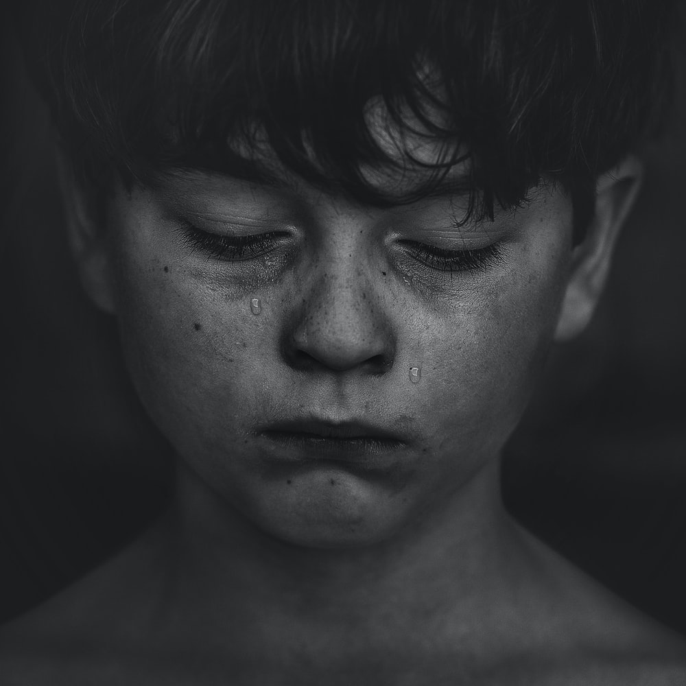彼の損失のために涙を流して泣いている男の子