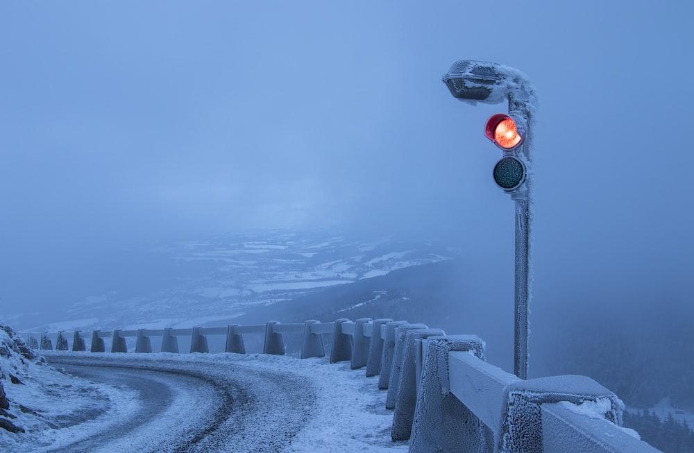 traffic light beside gray metal fence