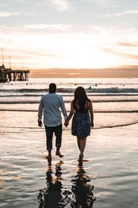 man and woman holding hands each other while walking on seashore during daytime