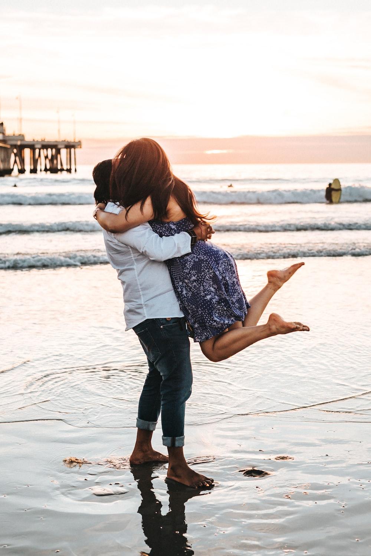man hugging woman on seashore