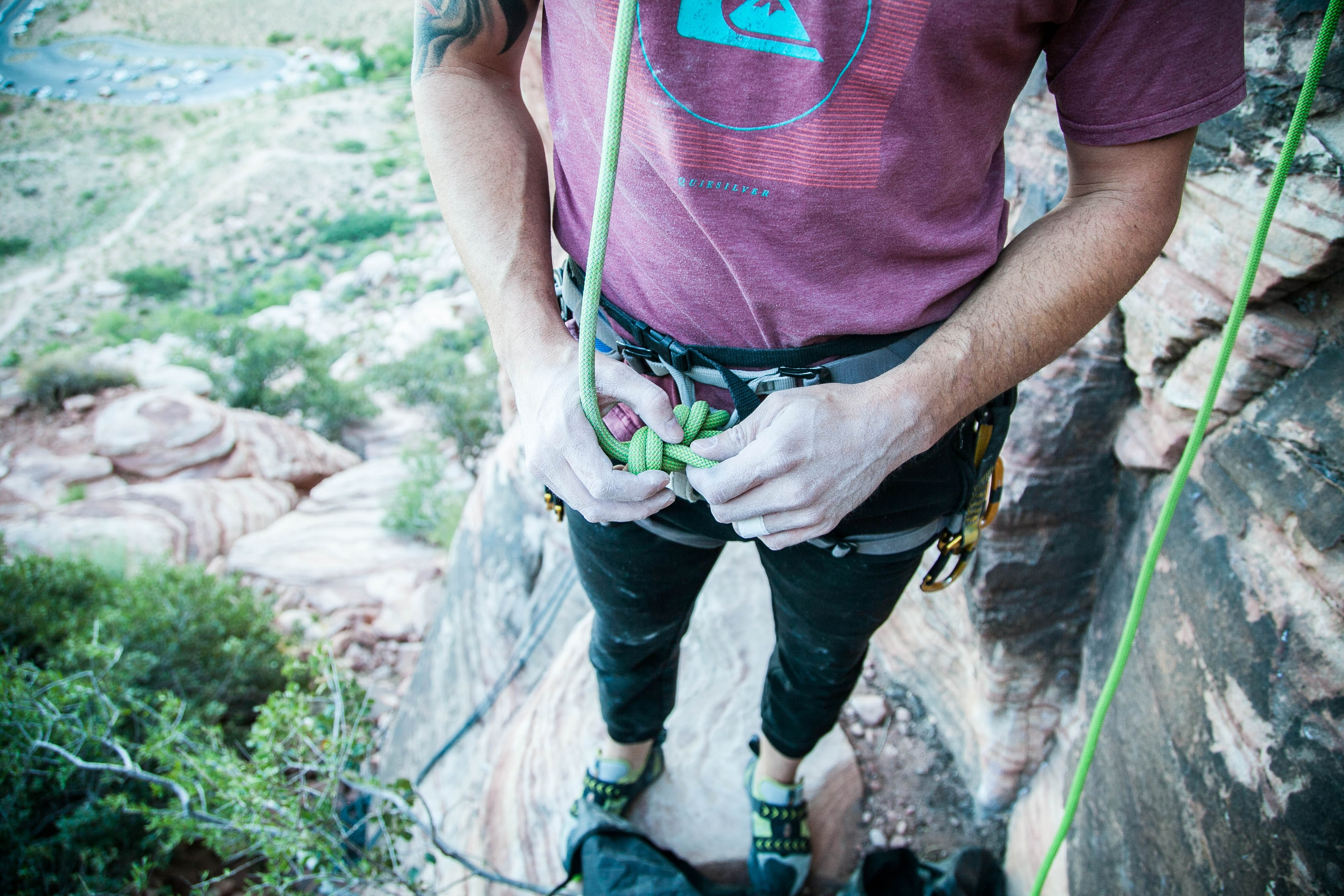 person holding green cable standing on mountain cliff