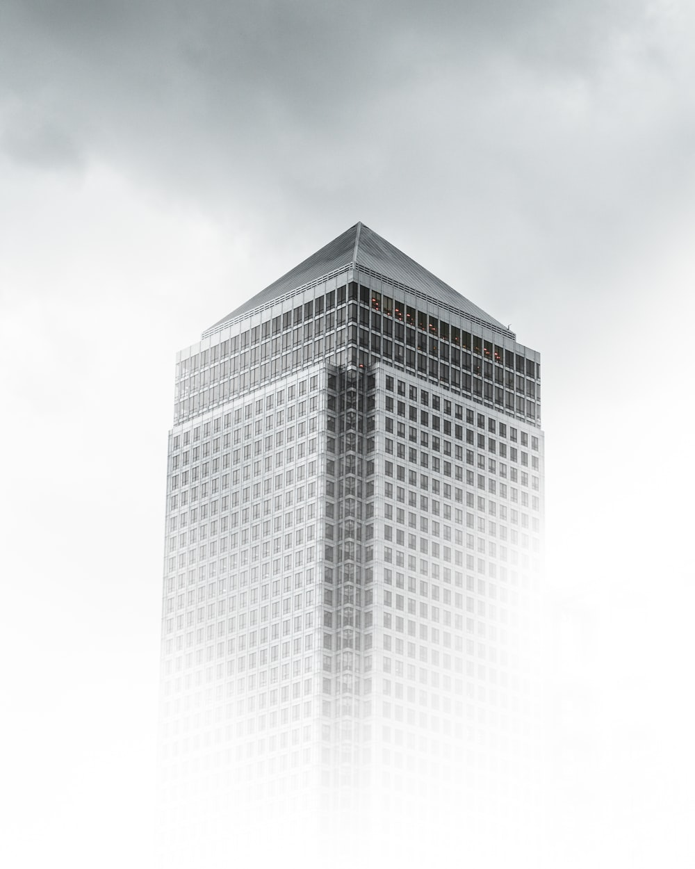 worm's-eye view photography of white and gray concrete building under cloudy sky