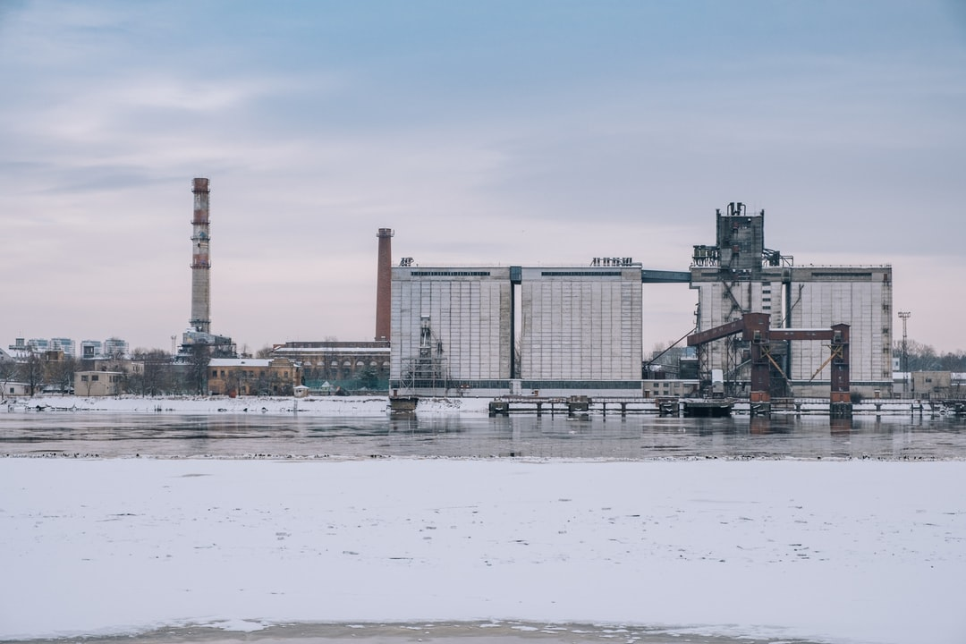 Look across the river to factories in cold winter day on January. Ice pieces floating in river.