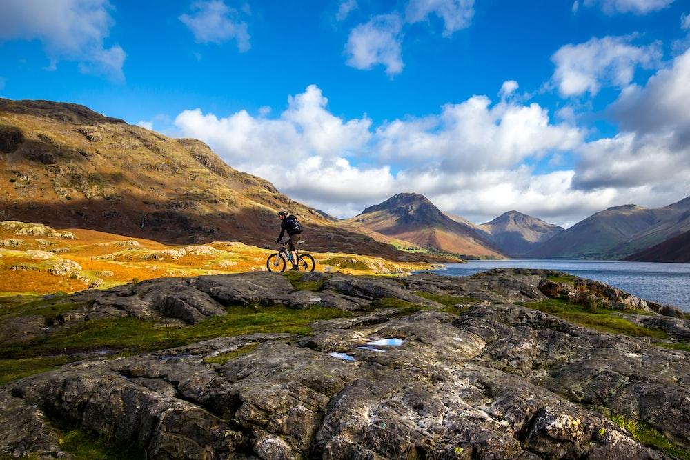 man riding bike through rocks