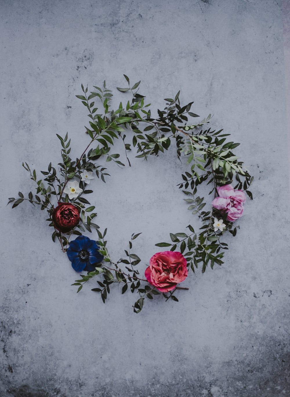 red, blue, and white flower wreath on white concrete