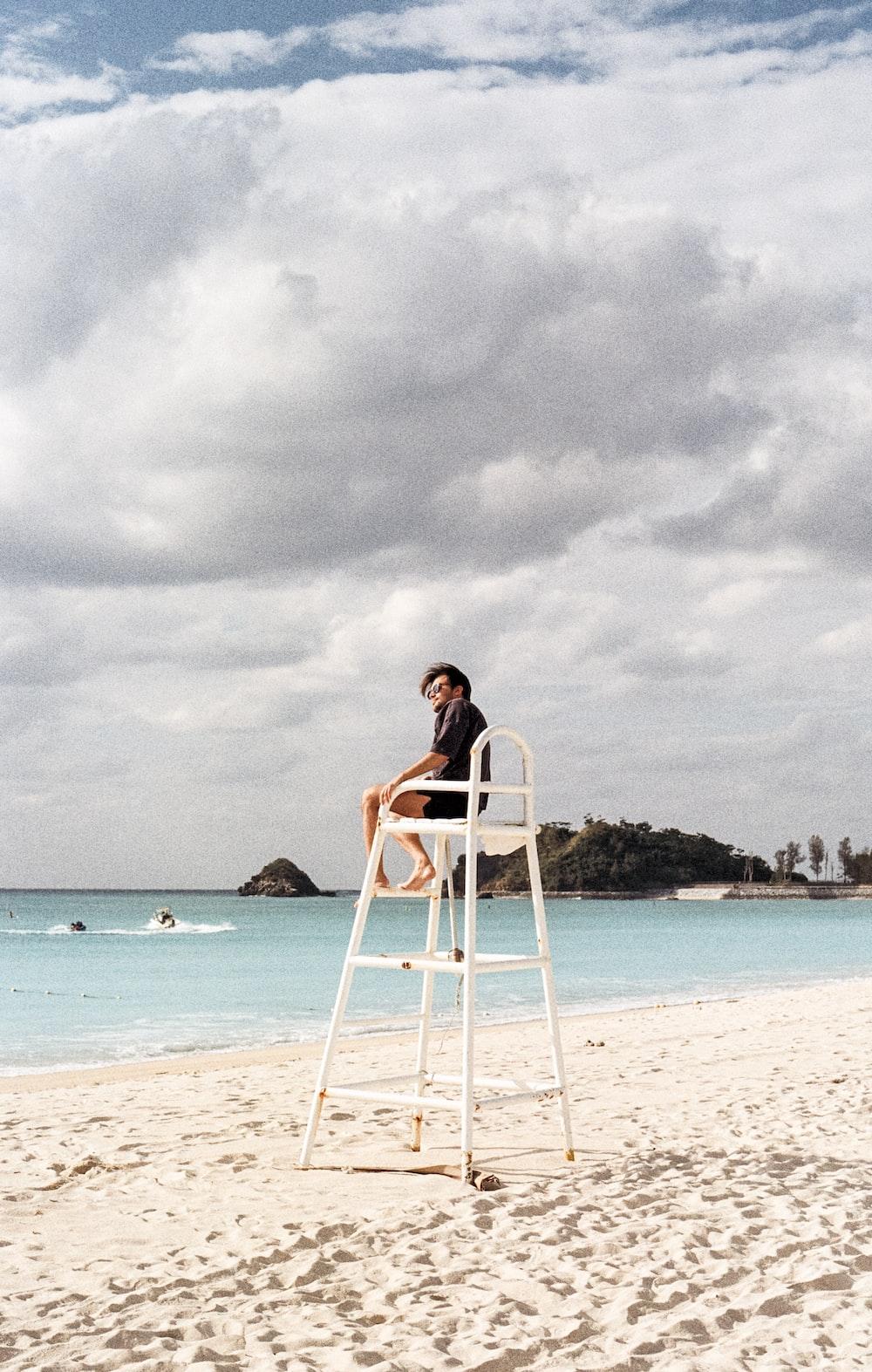 man sitting on lifeguard's chair