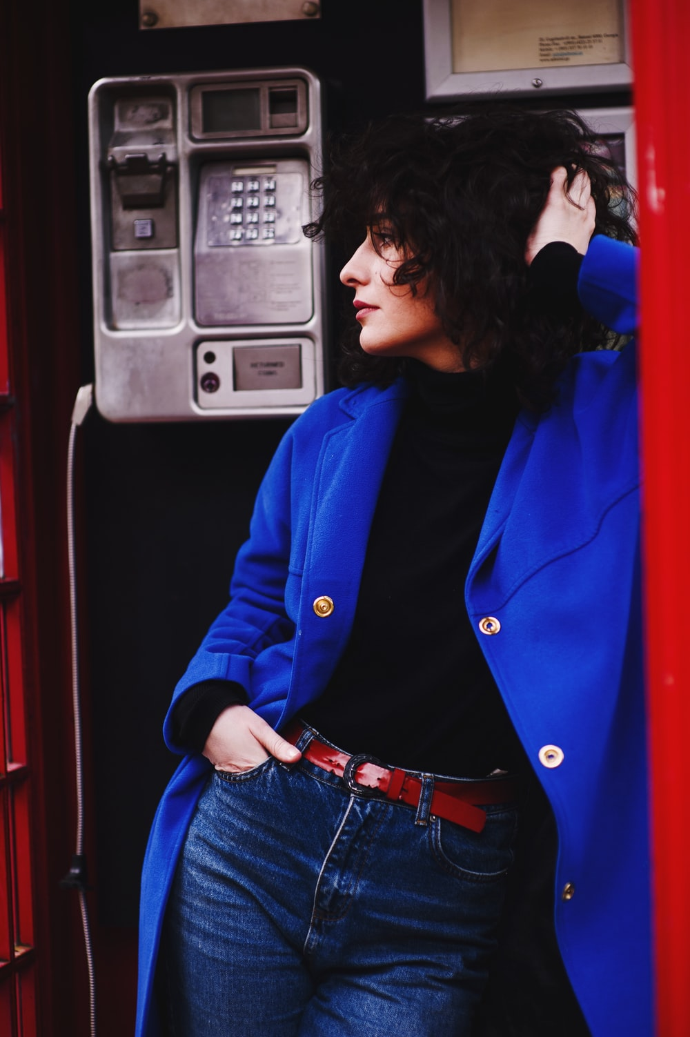 woman leaning on telephone booth wearing blue leather coat