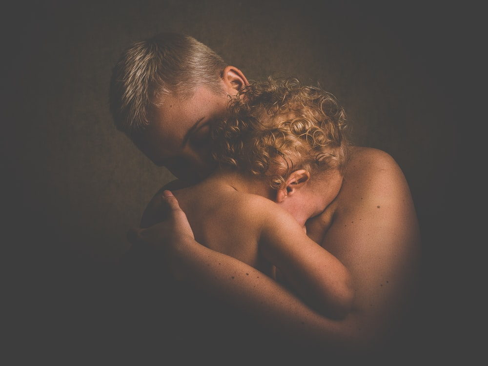 topless person carrying children