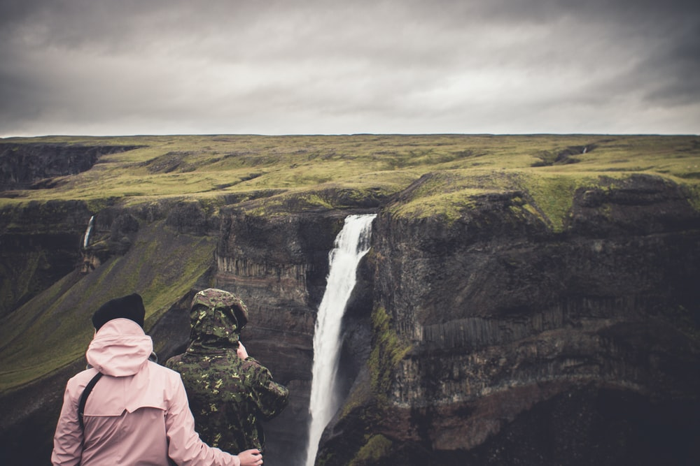 two person standing near the cliff watching the waterfalls
