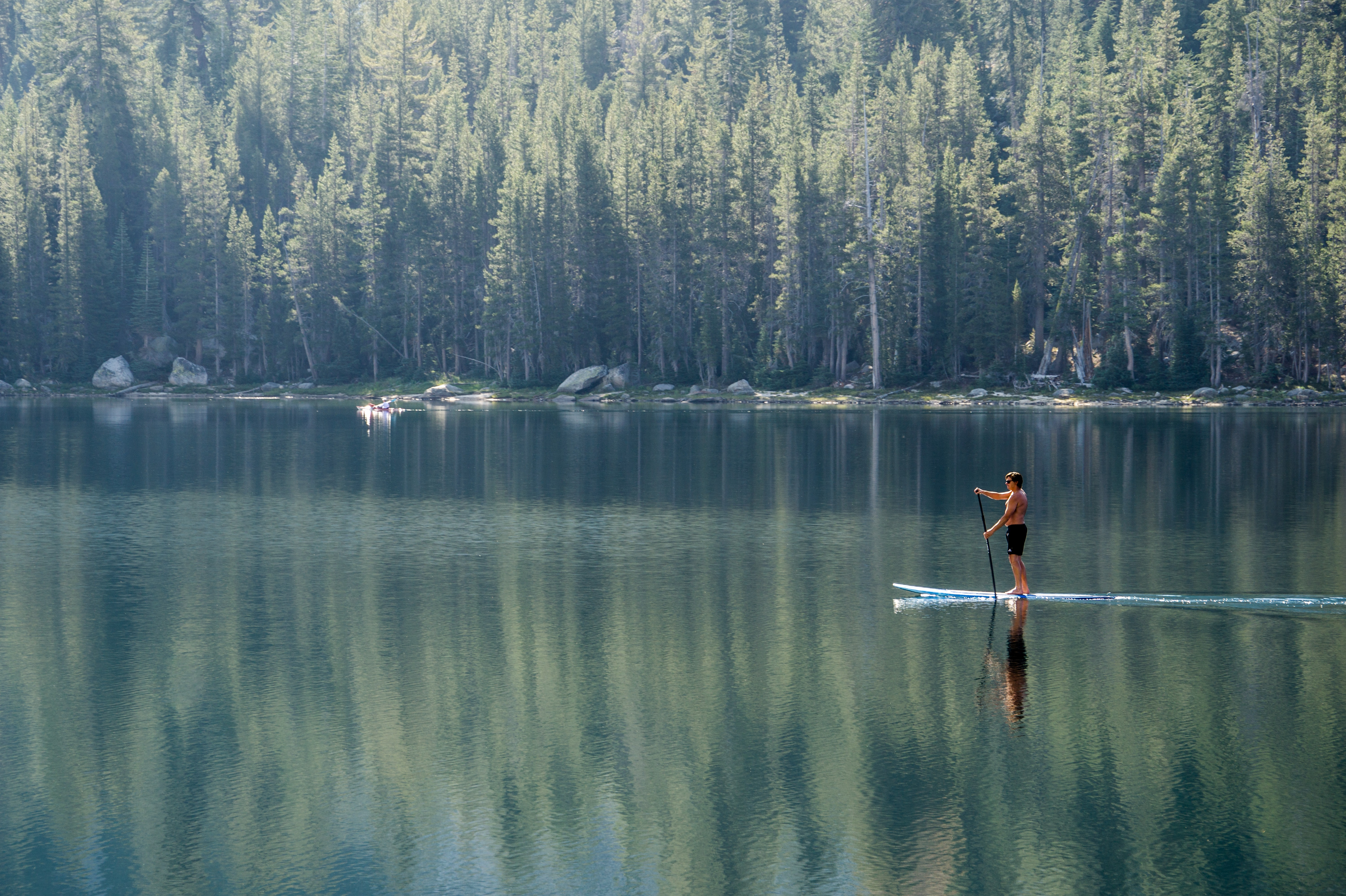 man standing on blue paddle board on body of water during daytime