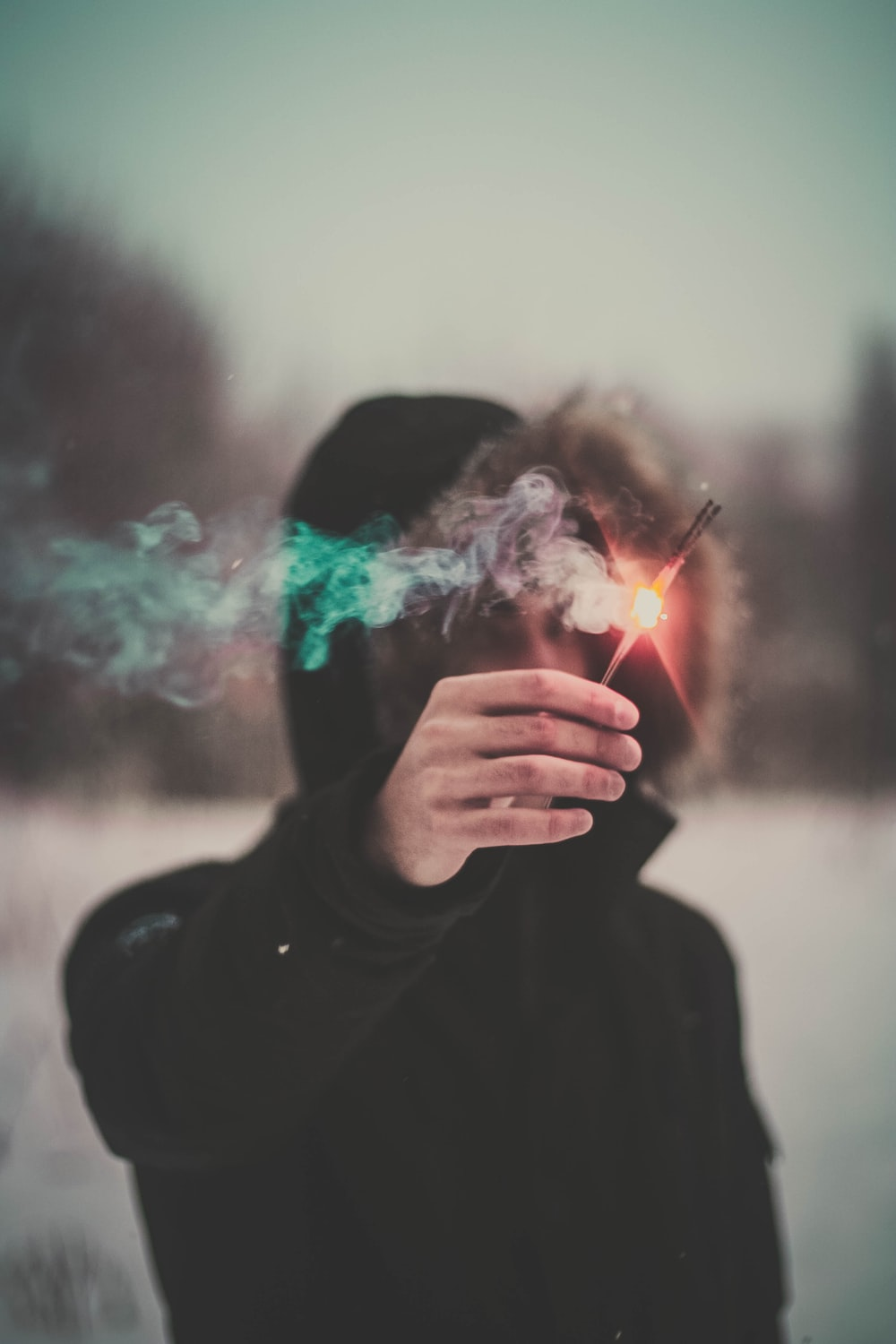 photo of person wearing hooded jacket holding lighted incense