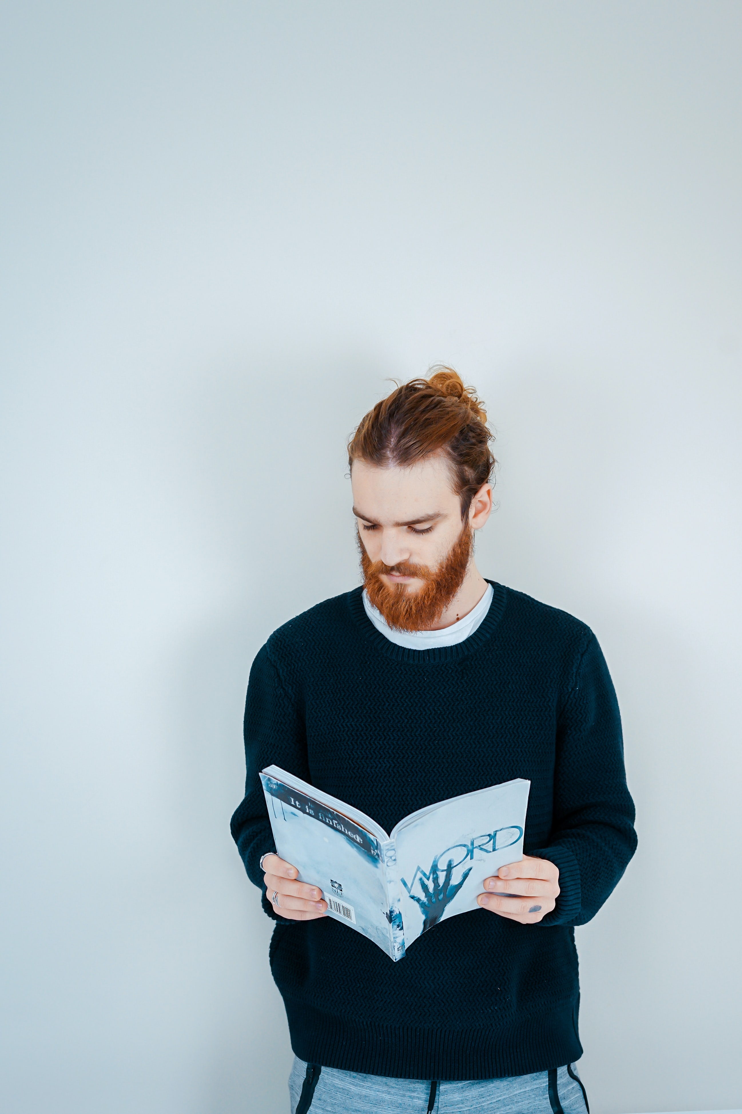 man reading book beside white wall