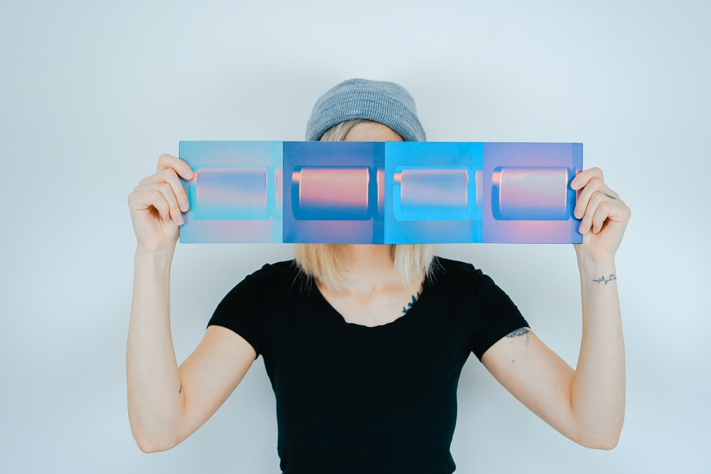 person holding blue paper covering her face