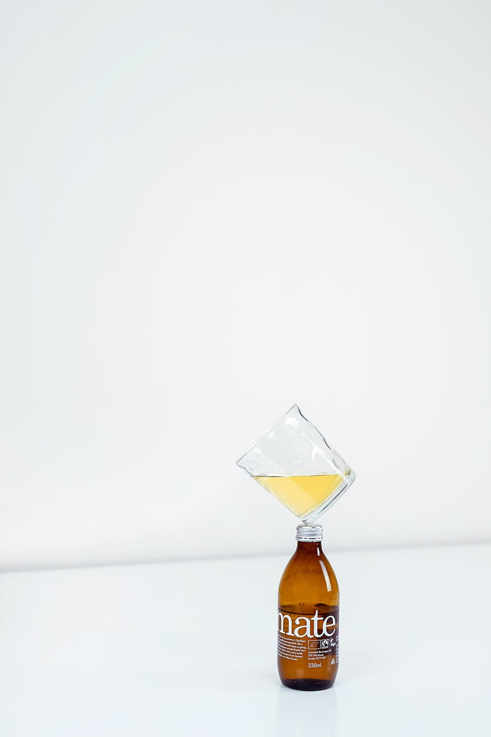 1/4 full clear drinking glass on top of amber bottle