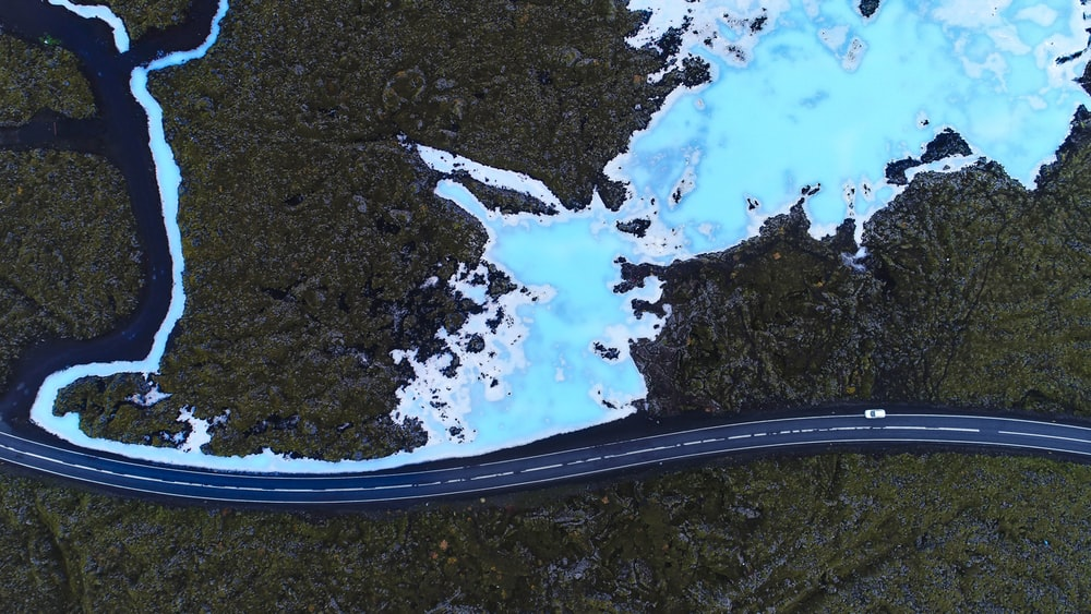 aerial view photo of vehicle crossing asphalt road between green trees near body of water
