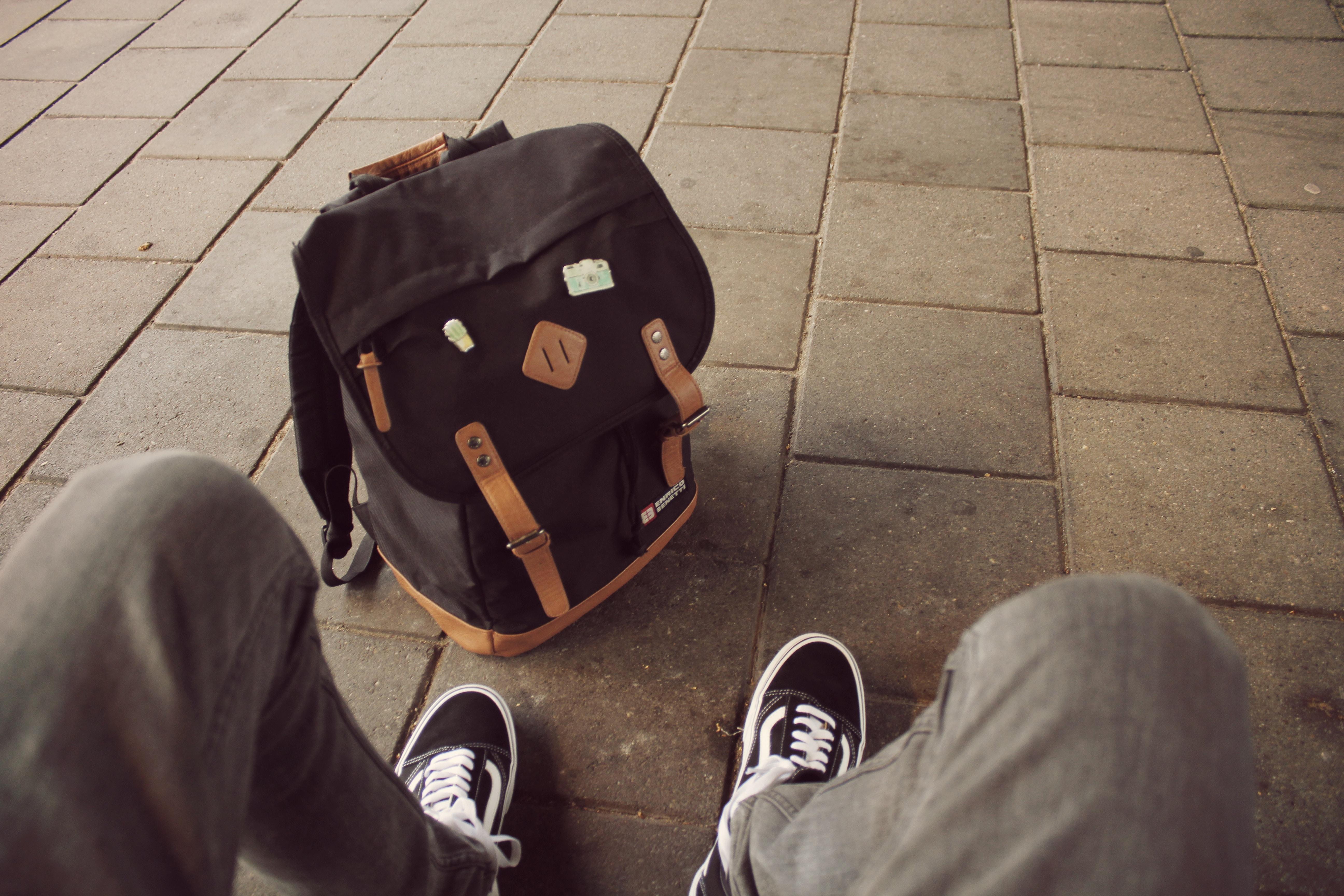 person wearing black-and-white Vans Old Skool sneakers
