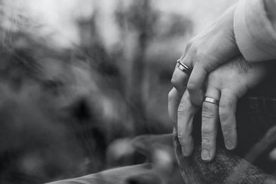 grayscale photo of two person holding hands with wedding rings marriage zoom background