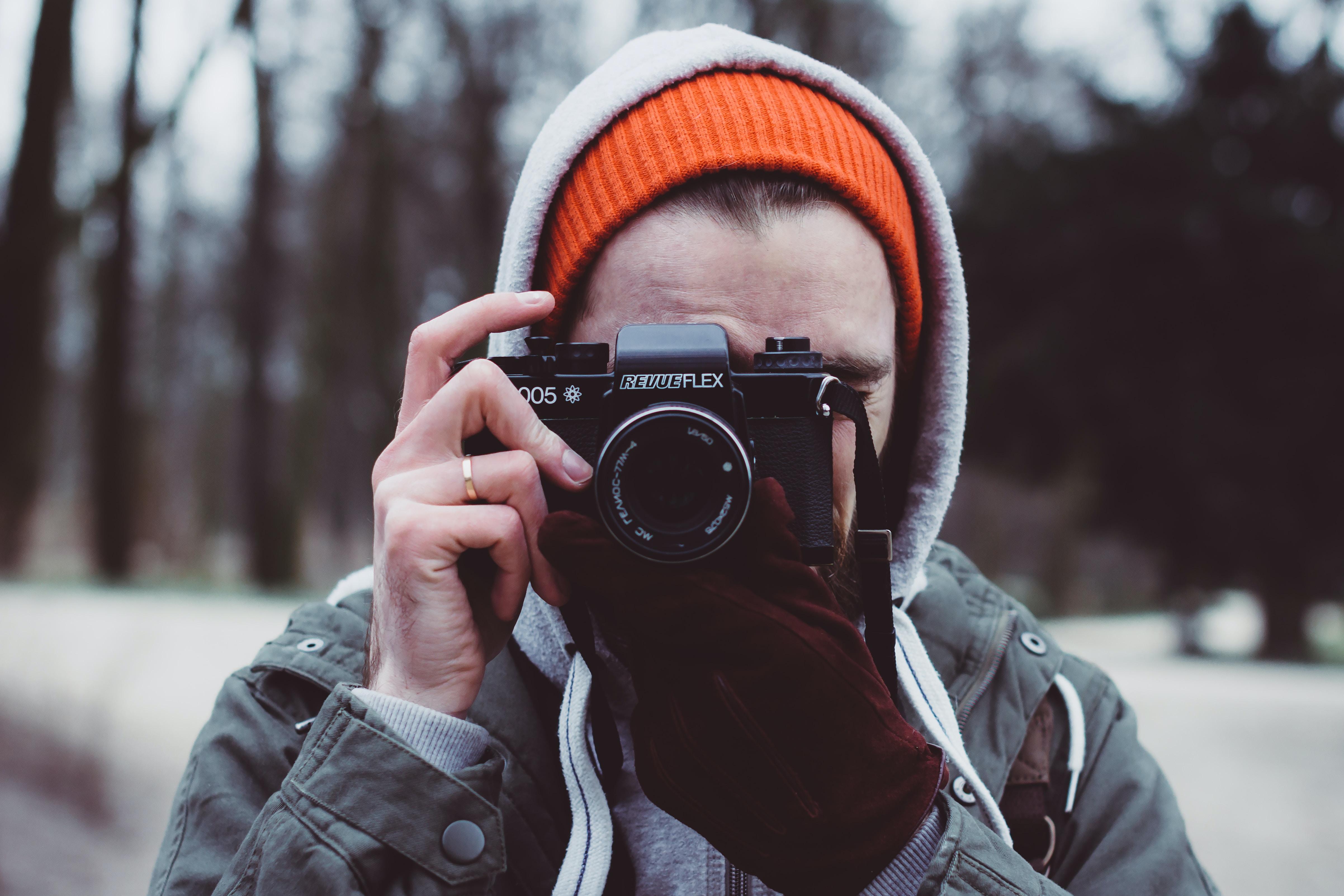 depth photography of man holding camera