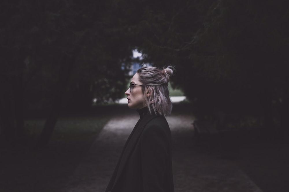 woman standing in between trees