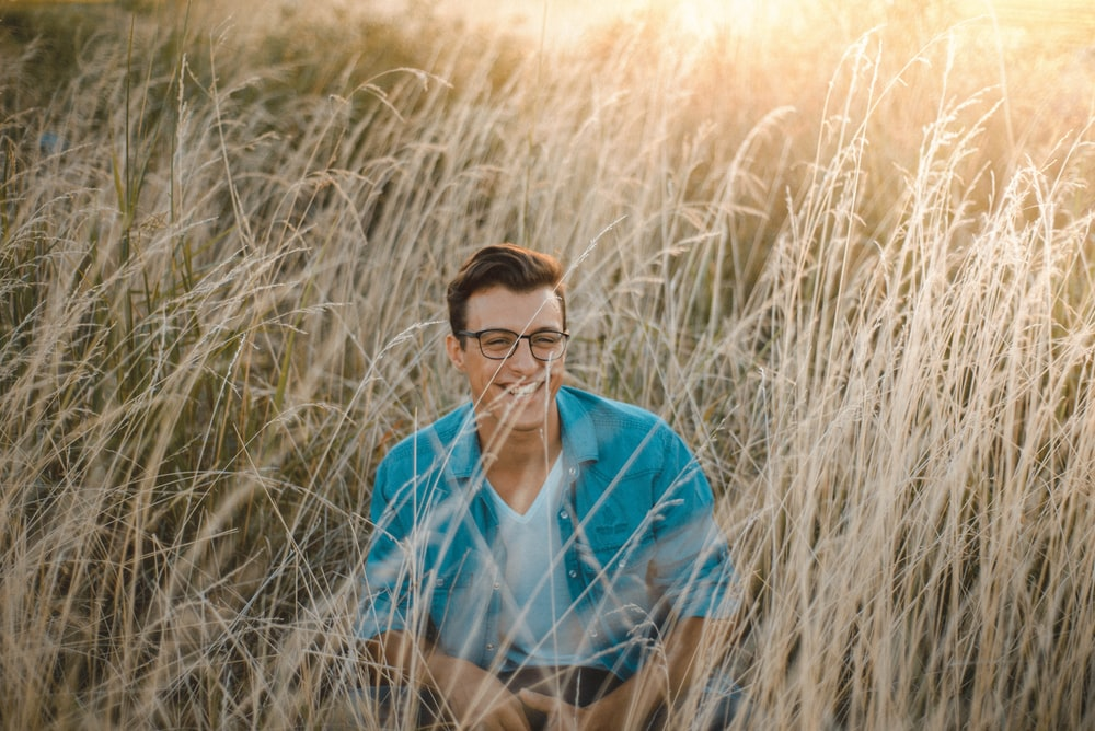 man sitting surrounded by grass during daytime