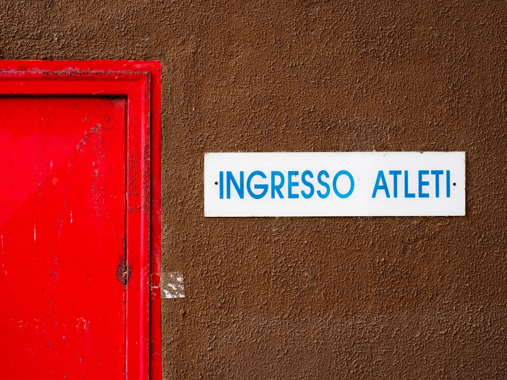 close-up photo of Ingresso Atleti signage beside door