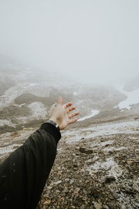 person rising their hand and facing at mountain