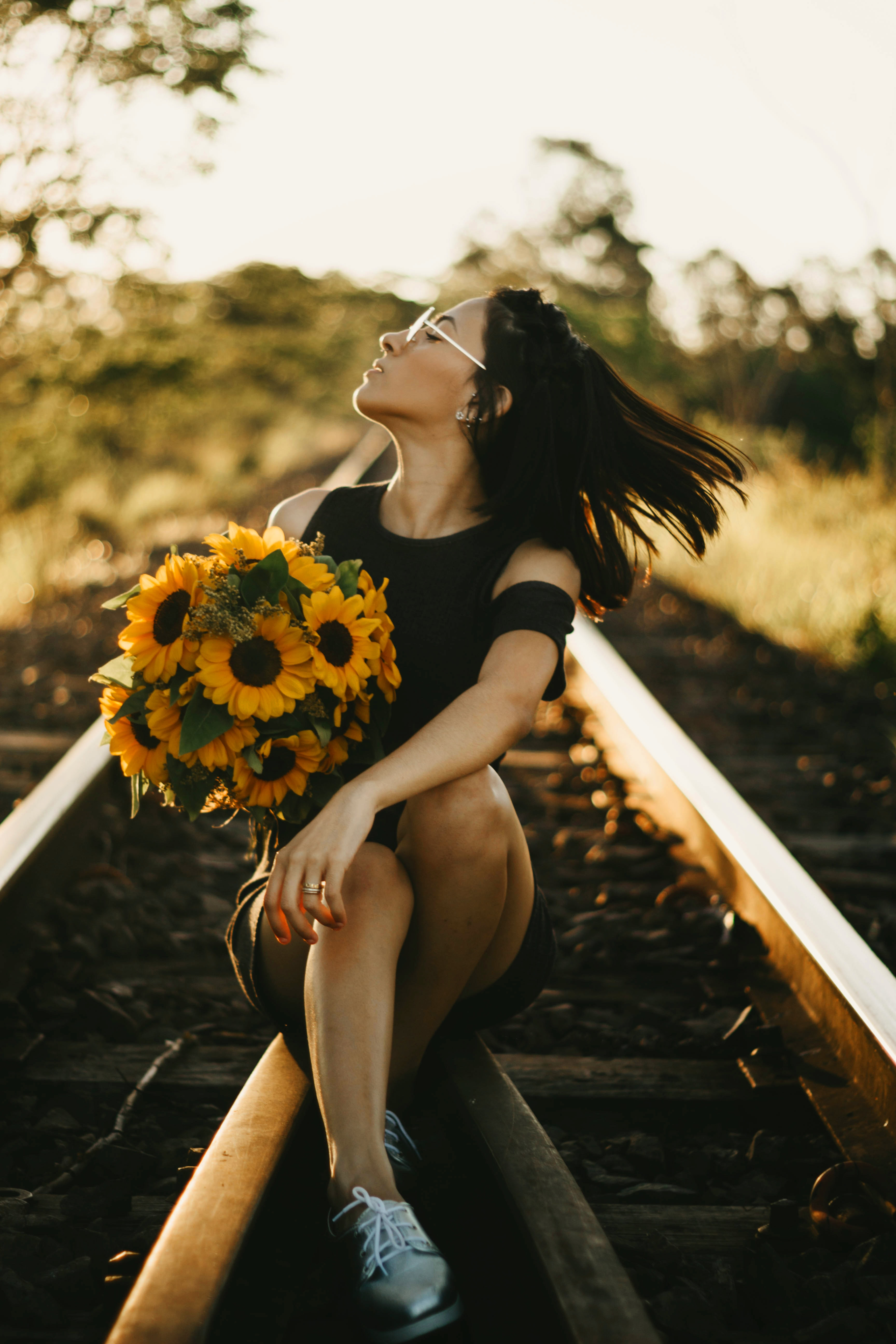 woman sitting on railroad holding bouquet of sunflowers
