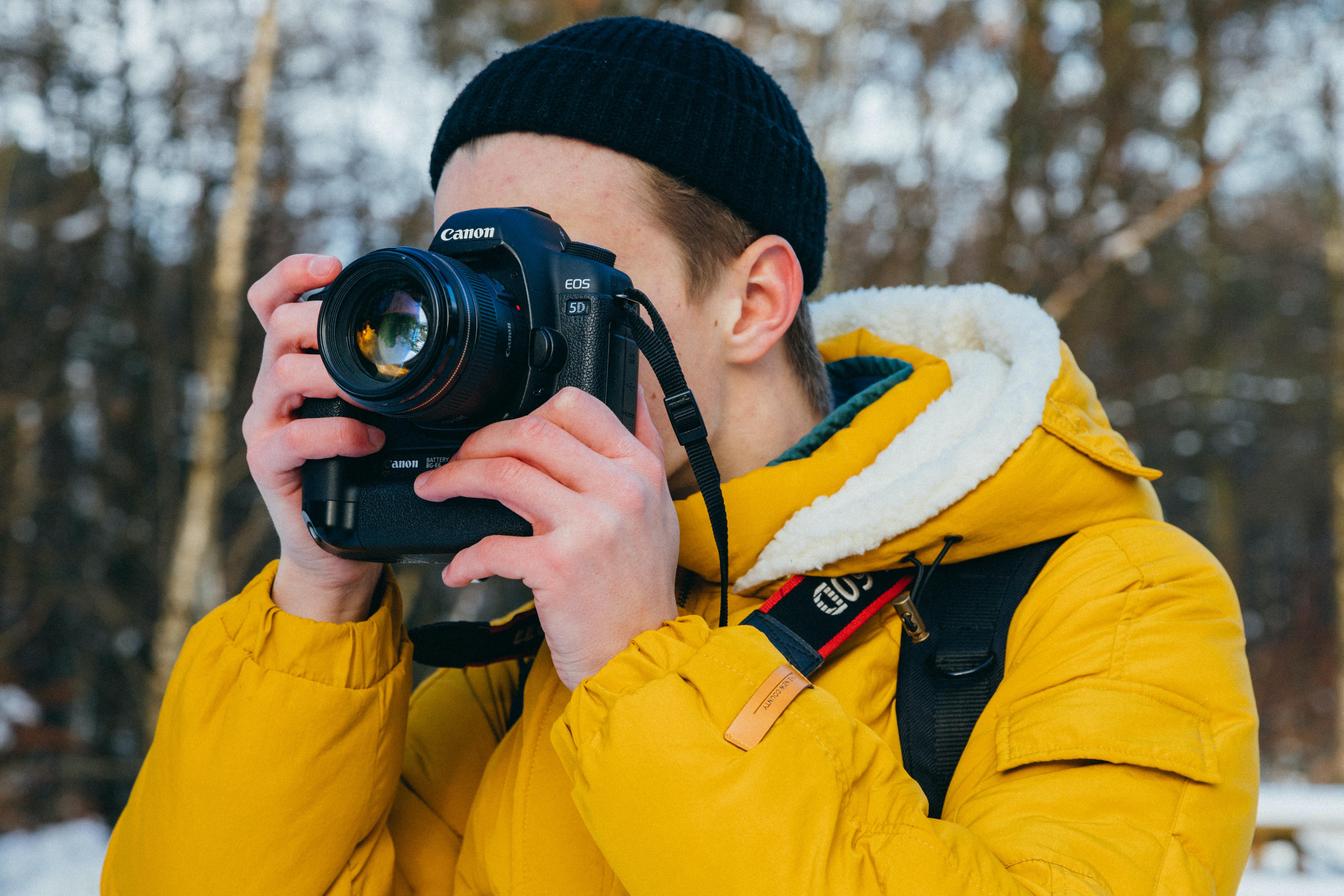 man using black Canon DSLR camera during daytime