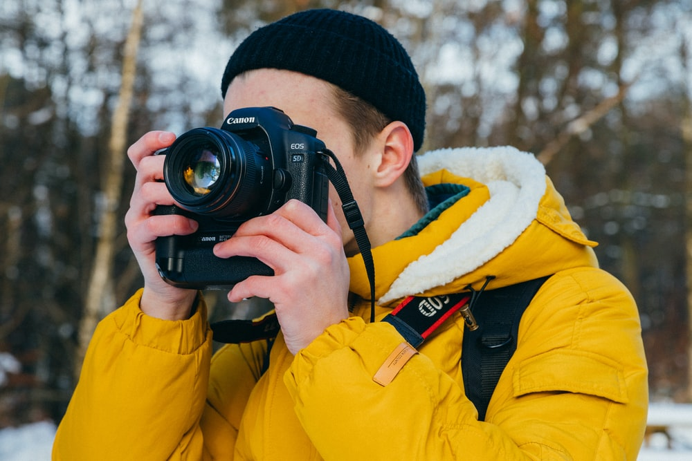 A man in a yellow coat and black hat with a camera in his hands