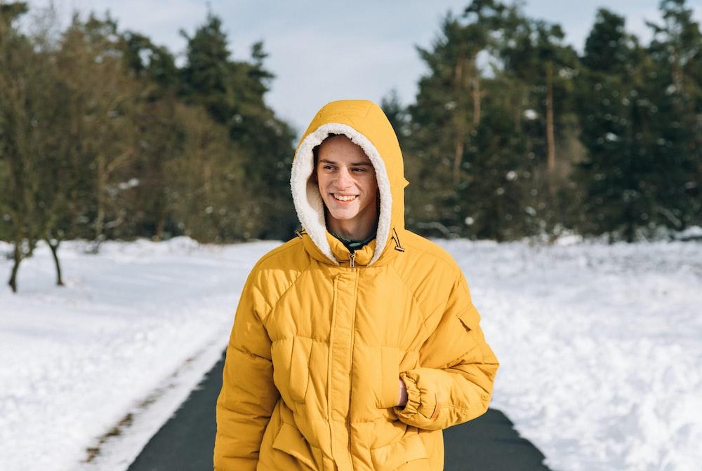 man standing on pathway in between snow field