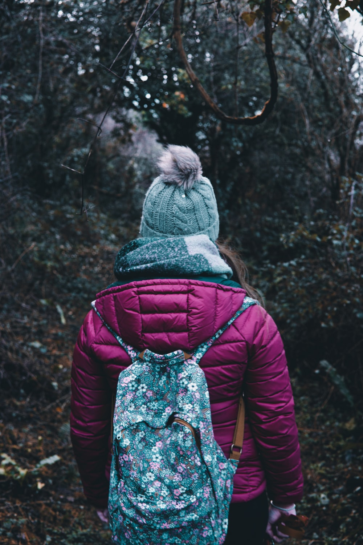 person walking between green trees