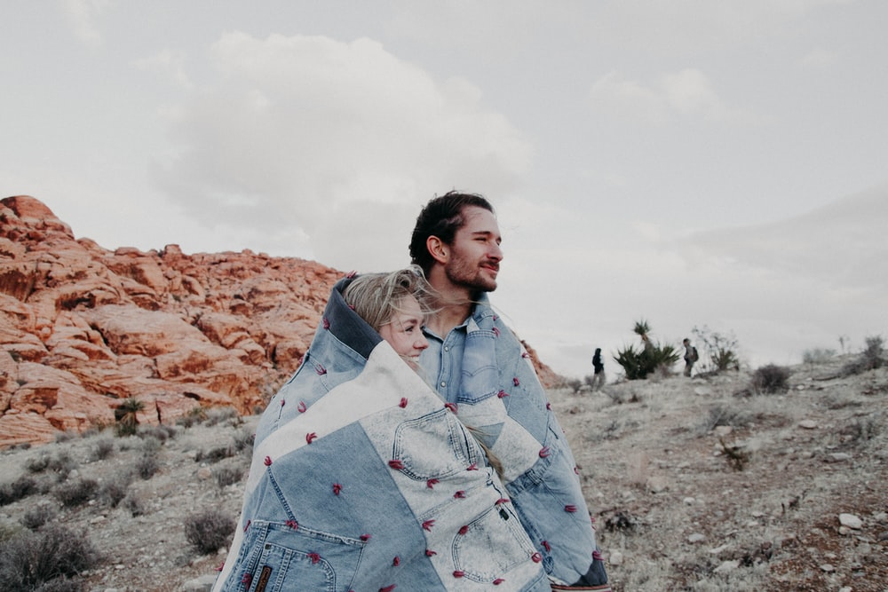 man and woman covered in blue blanket