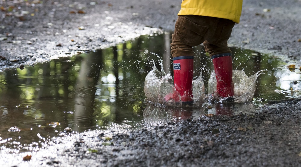 person in pair of red boots standing on water