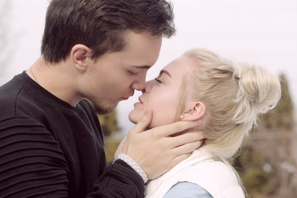 man wearing black top about to kiss woman