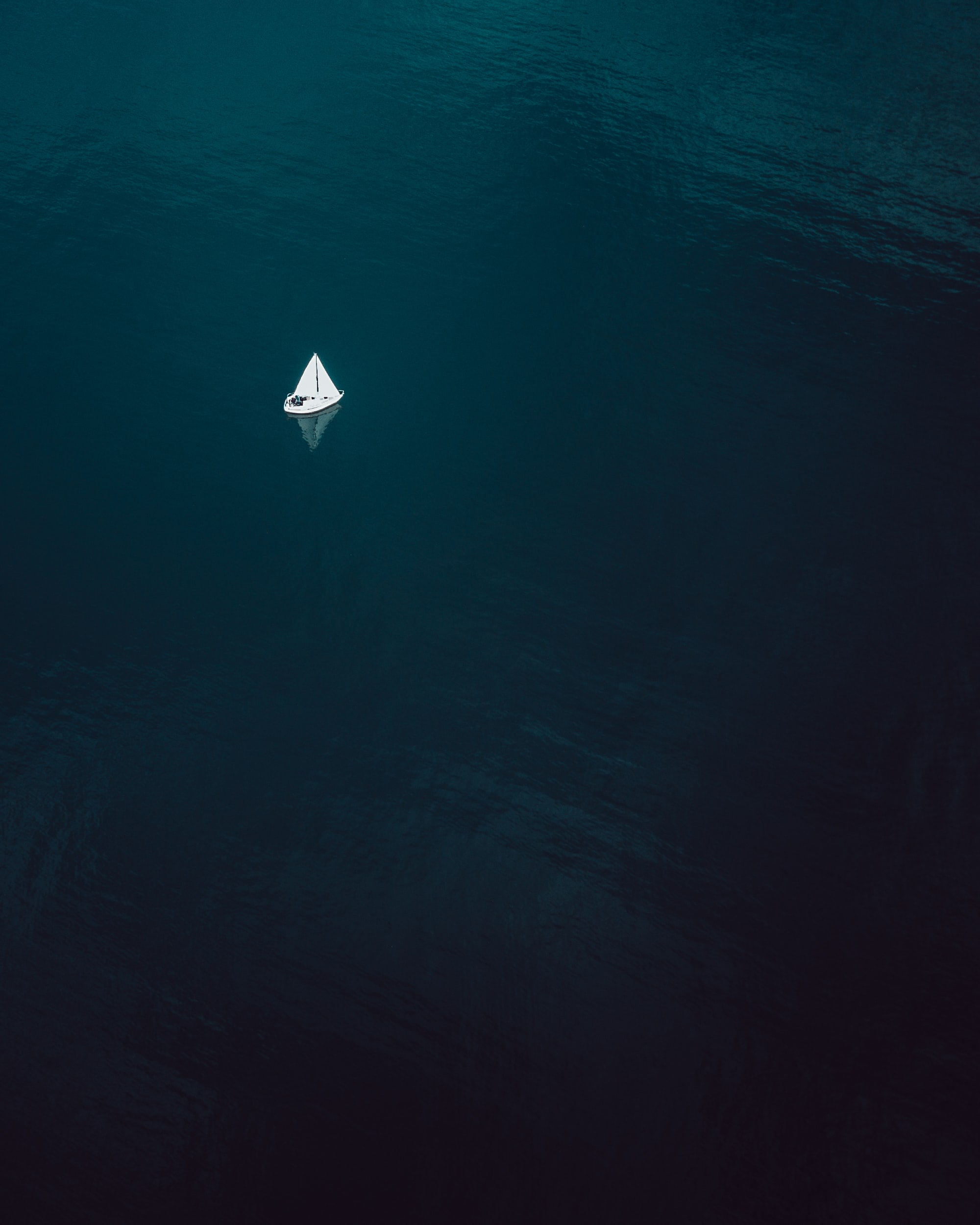 aerial photography of sailboat sailing on water body