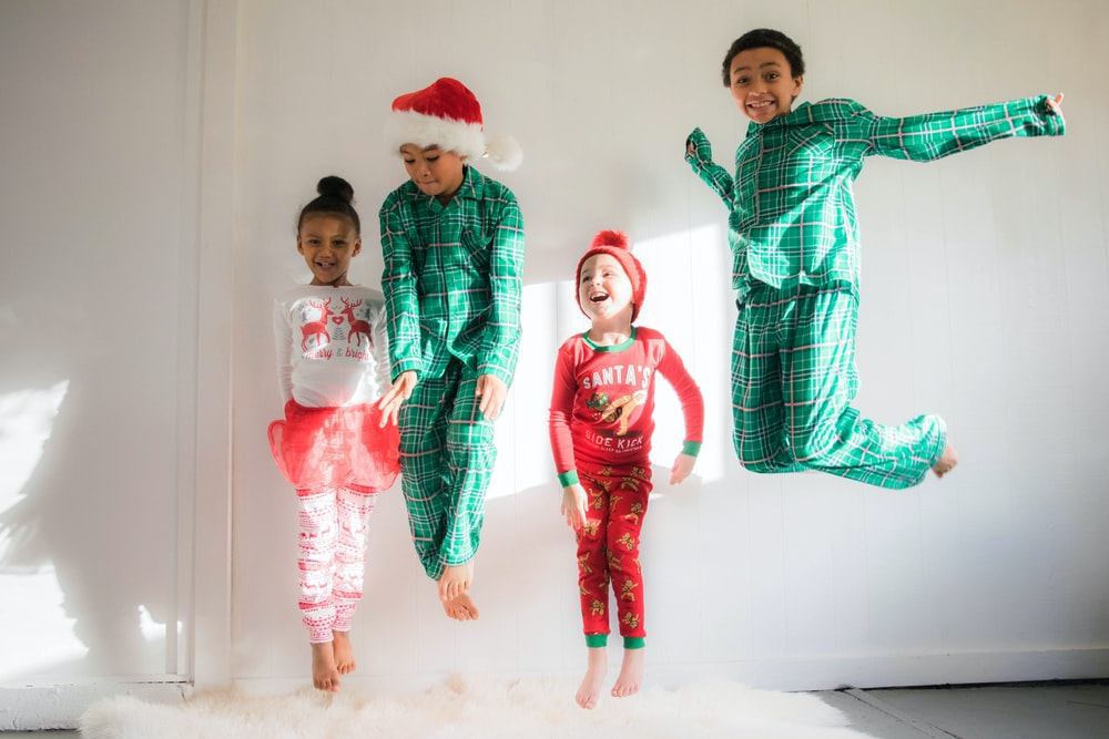 four kids doing jump shot inside bedroom while wearing pajamas