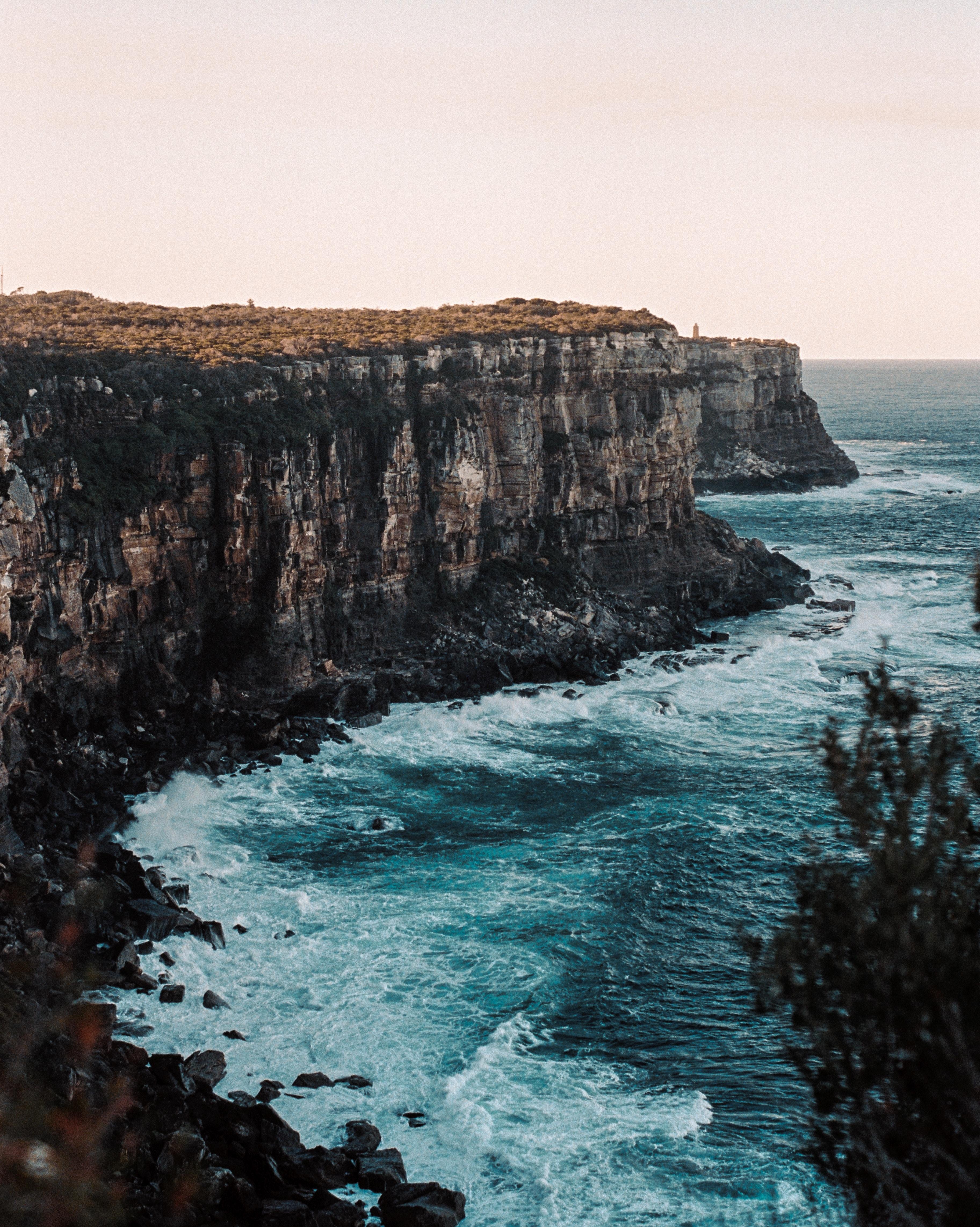 brown cliff near shoreline