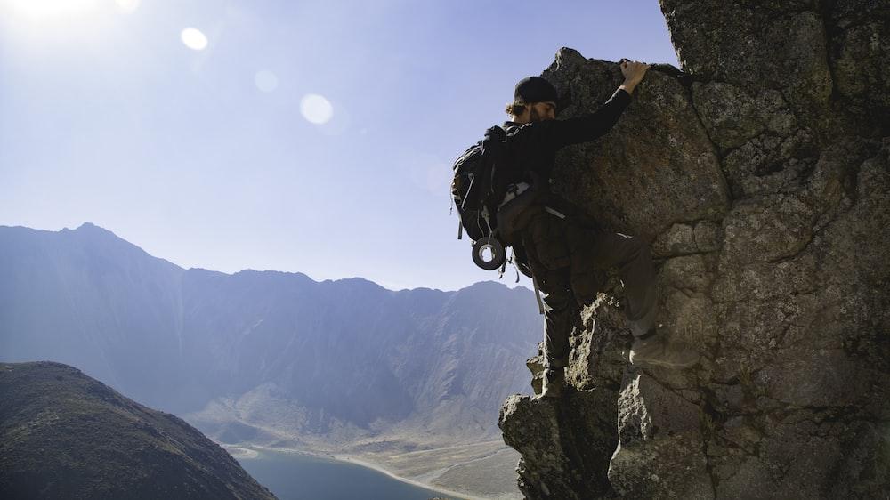 man climbing rock formation during daytime