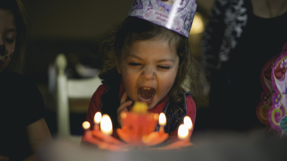 shallow focus photography of toddler blowing cake candles
