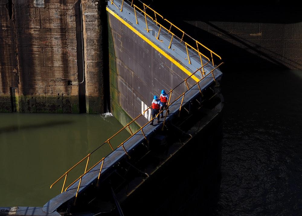 two persons walking on bridge