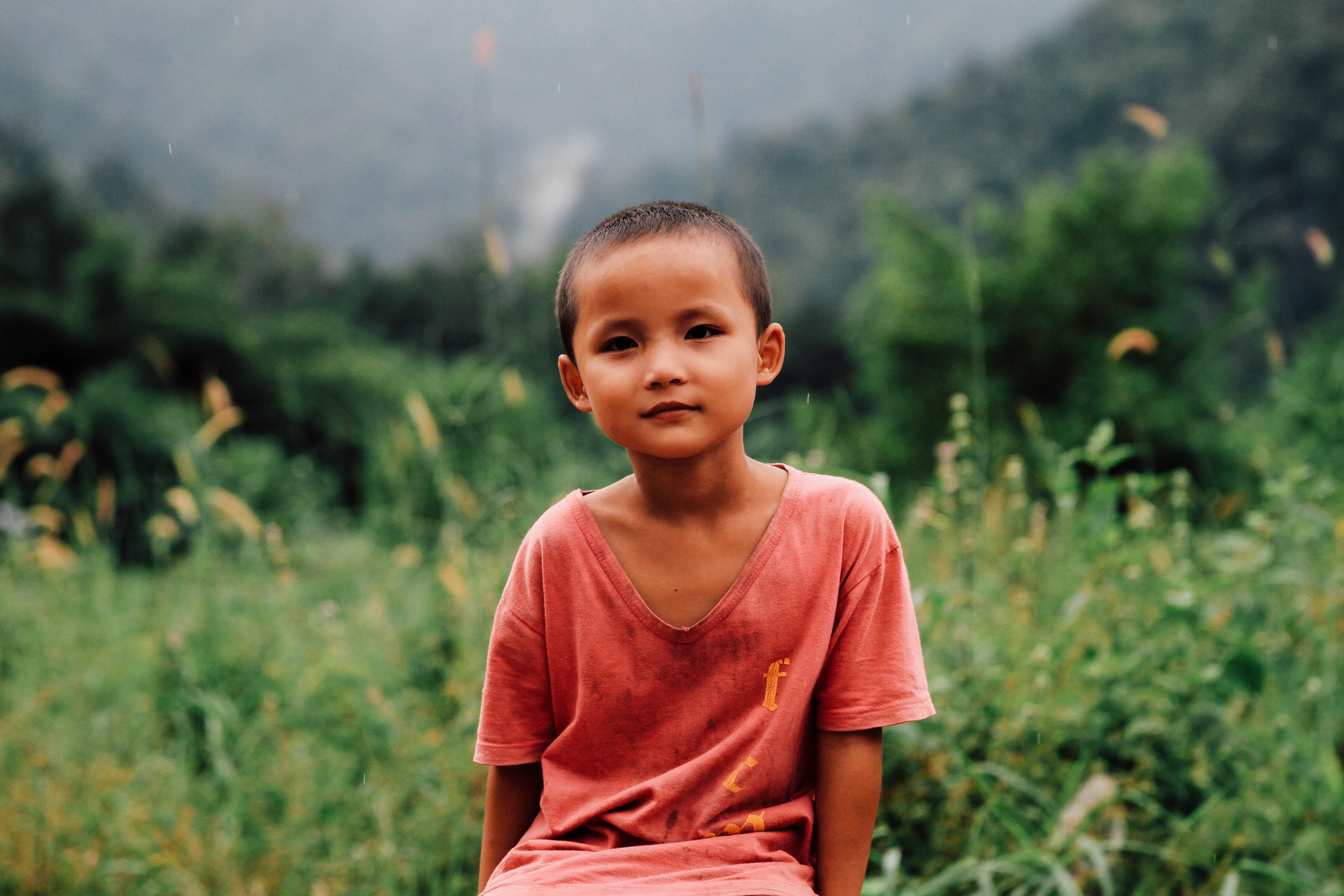 boy in red shirt sitting on grass