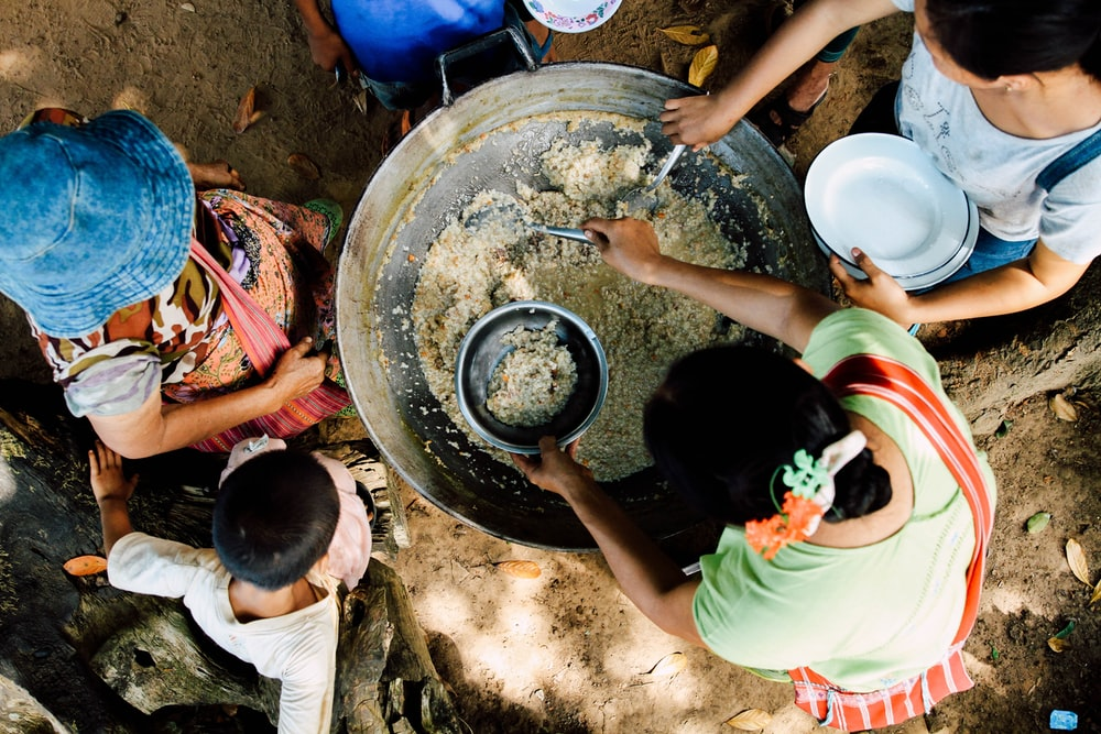 two women scooping rice in bowls