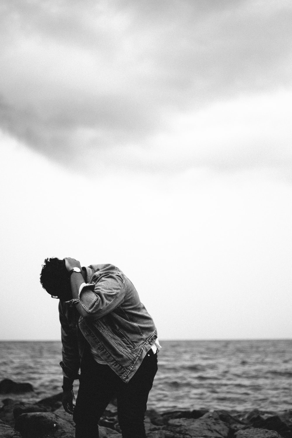 grayscale photography of person looking down at rocks