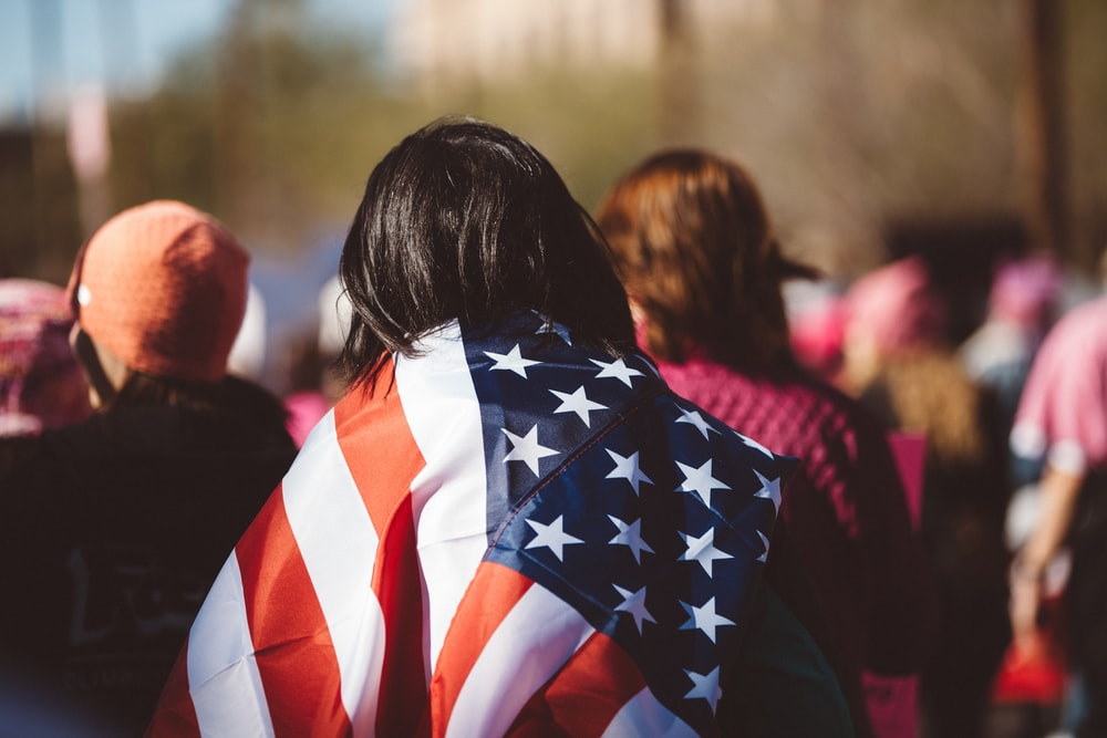 woman with US American flag on her shoulders