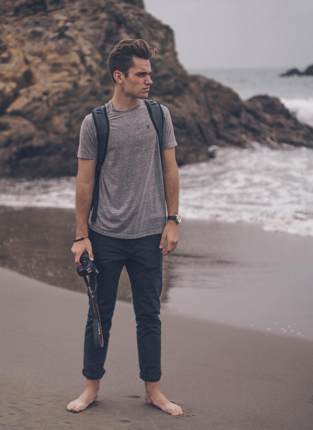 man holding DSLR camera on seashore near large rock