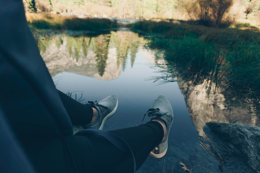 person sitting in front of body of water