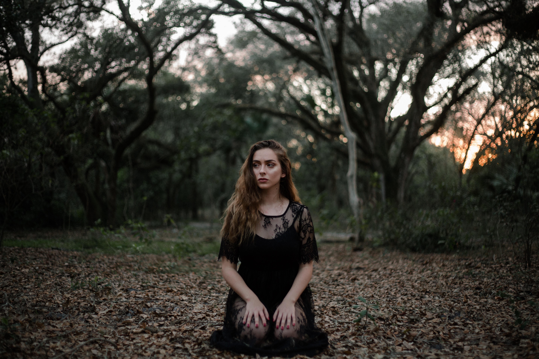 woman wearing black dress kneeling on ground