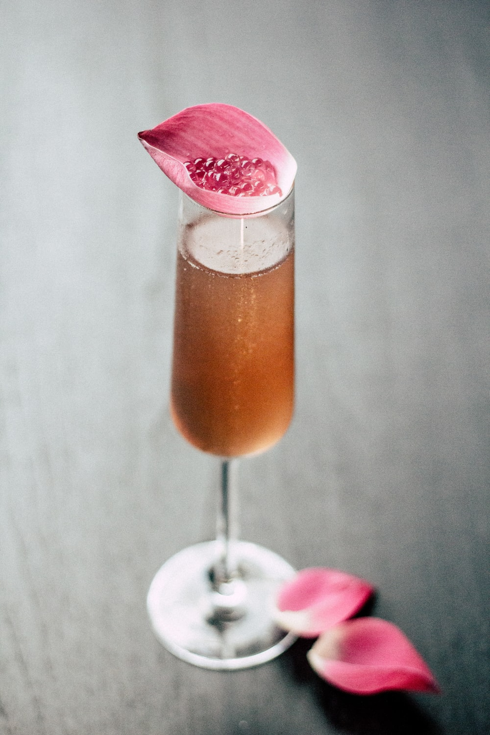 beverage in glass with pink leaf on top