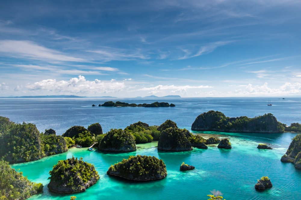 islets surrounded by body of water during daytime