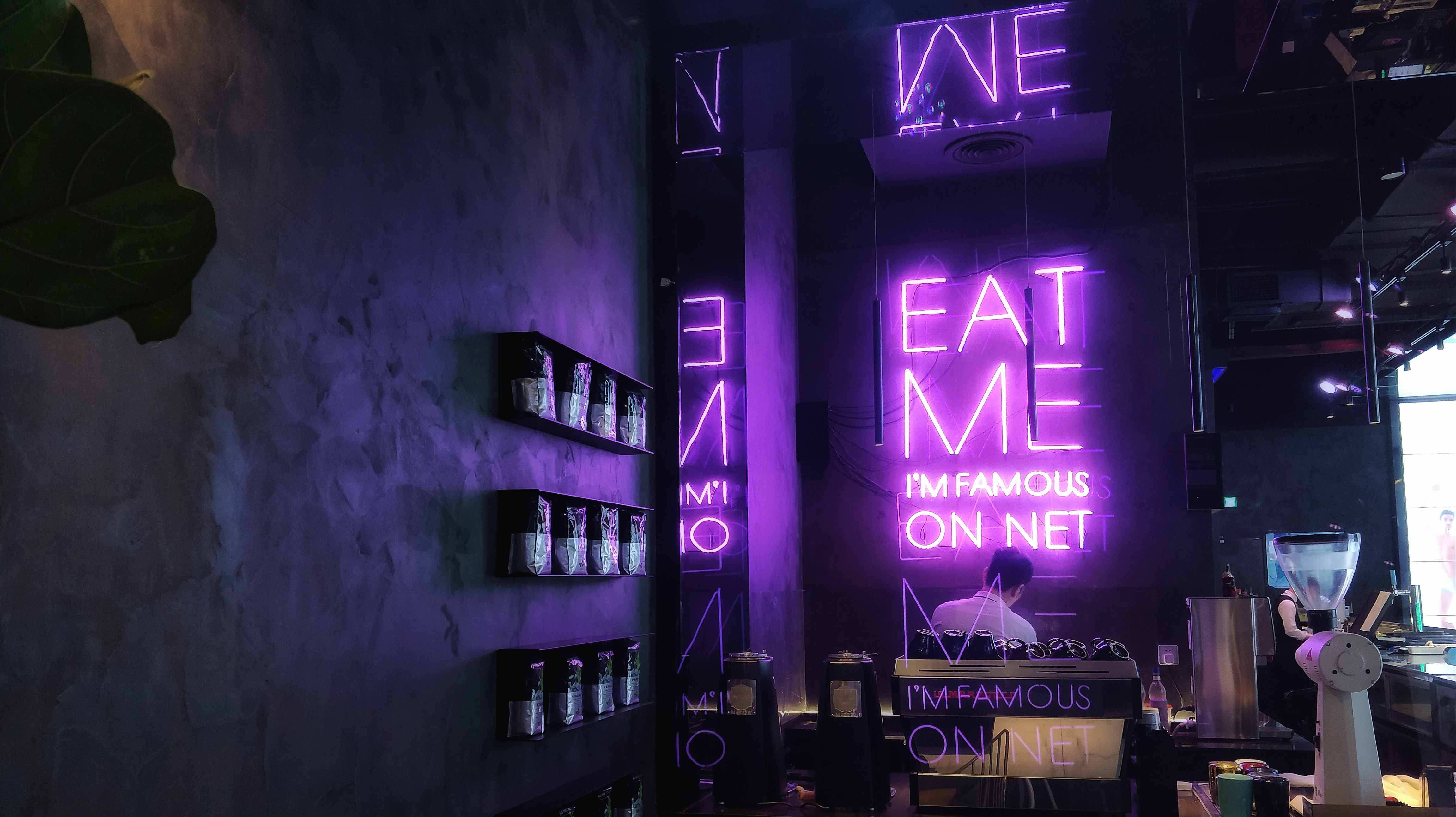 person sitting in front of purple Eat Me I'm Famous On Net LED signage